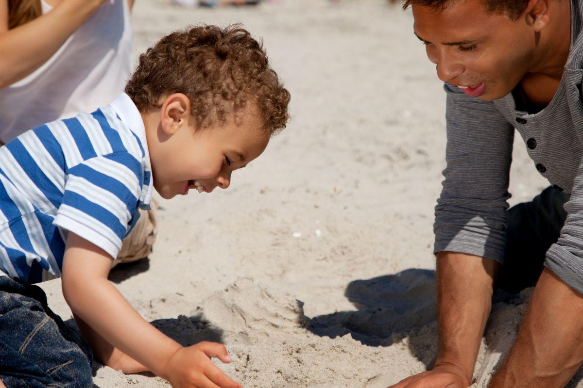 Kind mit Vater spielt im sand